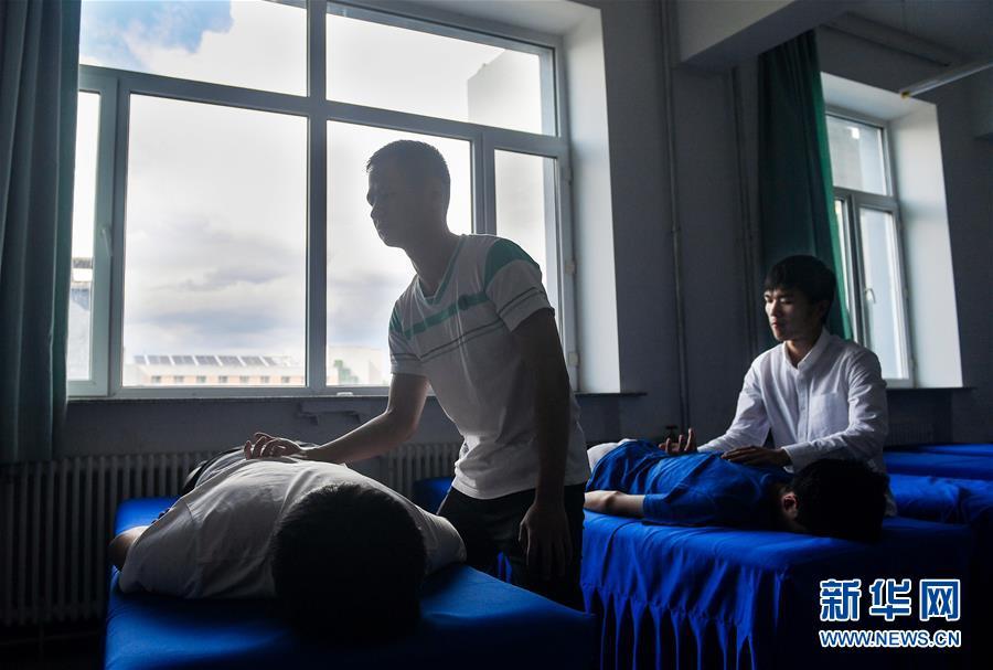 孙东远(右)和范长杰在教室内学习推拿按摩手法(6月20日摄)。新华社记者 许畅 摄